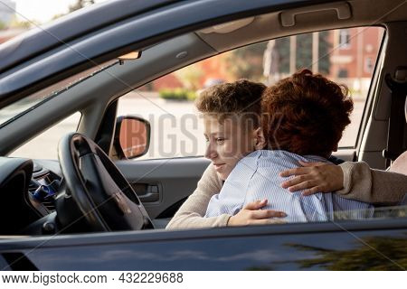 Schoolboy embracing his mother in the car before going to school in the morning