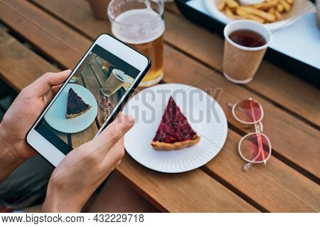 Hands of young female with smartphone taking photo of tasty cake on plate and drinks