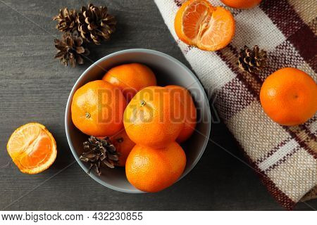 Bowl With Mandarins, Cones And Plaid On Dark Wooden Table