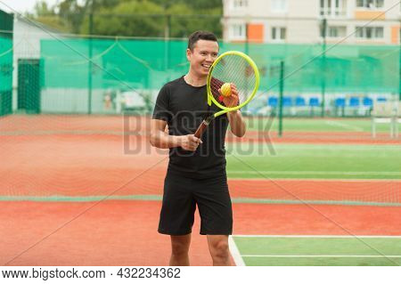 Cheerful Tennis Player On The Tennis Court Holds A Tennis Racket In His Hands And Prepares To Serve