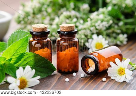 Bottles Of Homeopathy Granules. Homeopathic Remedies - Chamomilla, Mentha Piperita. Daisies Flowers