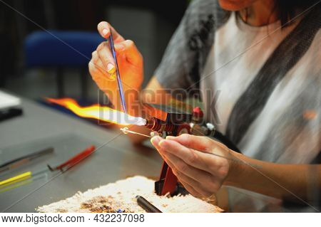 Work Of A Glassblower. Women's Hands Hold The Burner And Melt The Glass. Soft Selective Focus, Noise