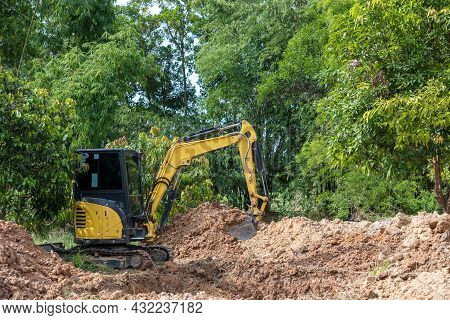 The Excavator Digs A Soil. Digger Loading Trucks With Soil. Excavator Working On Earthmoving At Open