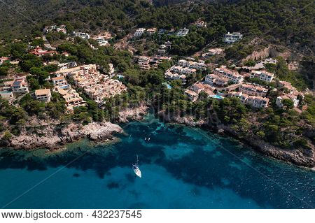 Top View Of Resort On Rocky Cliff In Canyamel, Cala Serch In Mallorca With Lonely Yacht On Turquoise