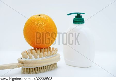 Orange On Double-sided Massage Brush For Body And Body Cream With Dispenser On White Background