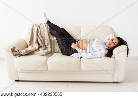Hispanic Pregnant Woman Lying On Sofa At Home. Pregnancy, Resting And Expectation Concept.