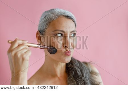 Funny Hoary Haired Asian Lady Applies Makeup With Brush Grimacing On Pink Background