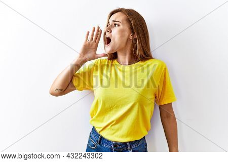 Young brunette woman standing over isolated background shouting and screaming loud to side with hand on mouth. communication concept.