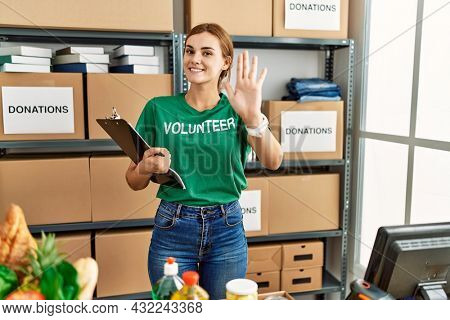 Young brunette woman wearing volunteer t shirt at donations stand waiving saying hello happy and smiling, friendly welcome gesture