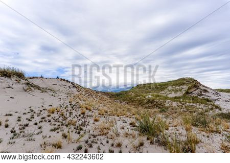 Sand Dune Landscape In Slowinski National Park With Grasses And Brush Under An Expressive Sky