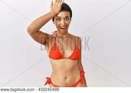 Young hispanic woman with short hair wearing bikini surprised with hand on head for mistake, remember error. forgot, bad memory concept.