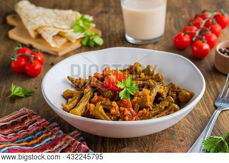 Stewed Okra With Tomatoes And Spices In A Clay Bowl On A Brown Wooden Background. Indian Food. Okra