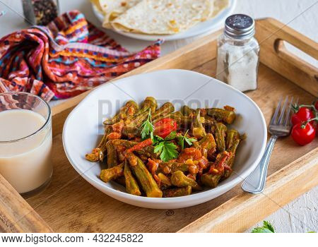 Stewed Okra With Tomatoes And Spices In A Clay Bowl On A Wooden Tray On A Light Concrete Background.