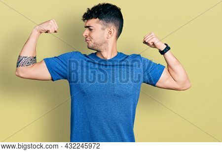 Young hispanic man wearing casual t shirt showing arms muscles smiling proud. fitness concept.
