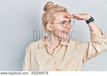 Beautiful caucasian woman with blond hair wearing casual look and glasses very happy and smiling looking far away with hand over head. searching concept.