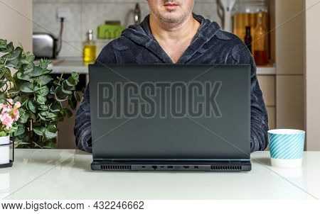 Trendy Mature Man Working From Home With Laptop Sitting At The Table In His Kitchen, Dressed In Bath