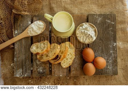 Ciabatta bread, flour and eggs on wooden background, baking ingredients, bakery
