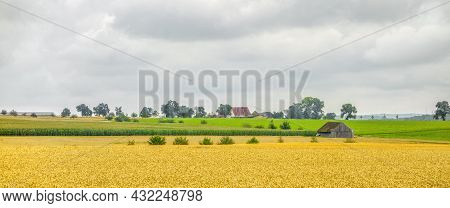 Agricultural Scenery With Barn And Fields And Farm Houses At Summer Time In Clouded Ambiance