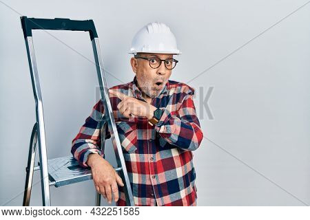 Handsome mature handyman close to construction stairs wearing hardhat surprised pointing with finger to the side, open mouth amazed expression.