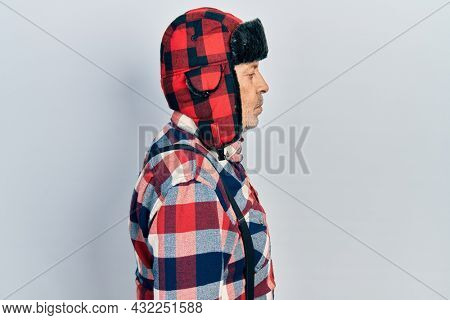 Handsome mature man wearing winter hat with ear flaps looking to side, relax profile pose with natural face with confident smile.