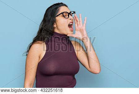 Brunette young woman wearing casual clothes and glasses shouting and screaming loud to side with hand on mouth. communication concept.