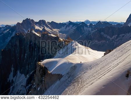 French Alps Mountains Snowy Ridge View With Silhouettes Of Climbers As Roping Team Descending On The