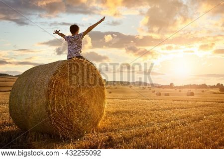 Boy sitting on a hay bale with arms raised in summer watching the sunset concept for worship, praise, religion or carefree childhood