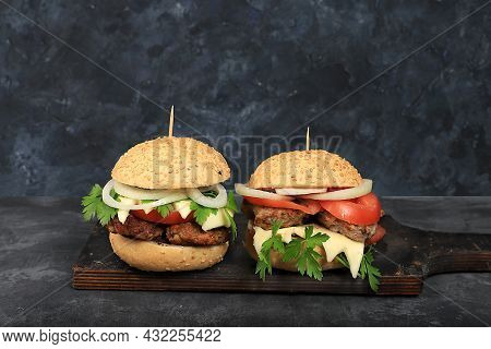 Two Cheeseburgers With Fresh Parsley Leaves, Tomatoes, Cream Cheese, Onions And Cutlet On An Old Con