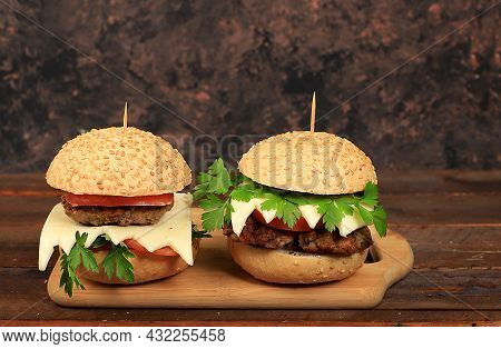 Two Cheeseburgers With Fresh Parsley Leaves, Tomatoes, Cream Cheese, Onions And Cutlet On An Old Woo