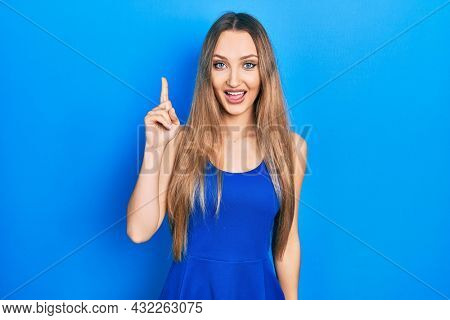 Young blonde girl wearing casual clothes pointing finger up with successful idea. exited and happy. number one.