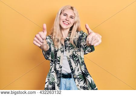 Beautiful caucasian woman with blond hair wearing tropical shirt approving doing positive gesture with hand, thumbs up smiling and happy for success. winner gesture.