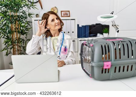 Middle age veterinarian woman working at pet clinic smiling with hand over ear listening an hearing to rumor or gossip. deafness concept.