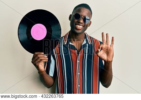 Young african american man wearing hippie style holding vinyl disc doing ok sign with fingers, smiling friendly gesturing excellent symbol