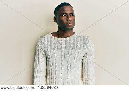 Young african american man wearing casual clothes smiling looking to the side and staring away thinking.