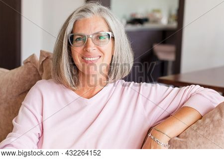 Portrait of smiling mature woman with glasses looking at camera. Successful middle aged woman sitting on couch at home. Beautiful smiling middle adult lady with gray hair at home