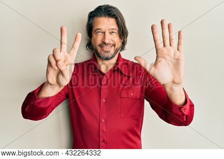 Middle age handsome man wearing casual clothes showing and pointing up with fingers number seven while smiling confident and happy.