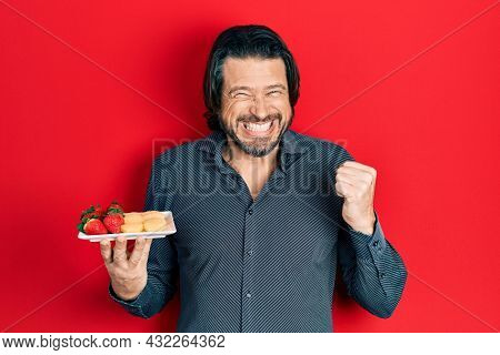Middle age caucasian man eating fresh and healthy fruit screaming proud, celebrating victory and success very excited with raised arm