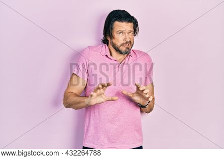Middle age caucasian man wearing casual white t shirt disgusted expression, displeased and fearful doing disgust face because aversion reaction.