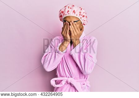 Hispanic man wearing make up wearing shower towel cap and bathrobe rubbing eyes for fatigue and headache, sleepy and tired expression. vision problem