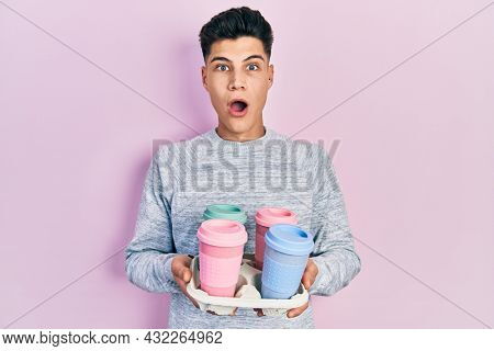 Young hispanic man holding tray with take away coffee afraid and shocked with surprise and amazed expression, fear and excited face.