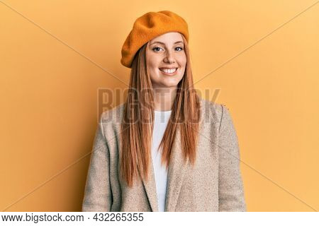 Young irish woman wearing french look with beret looking positive and happy standing and smiling with a confident smile showing teeth