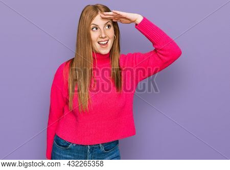 Young irish woman wearing casual clothes very happy and smiling looking far away with hand over head. searching concept.