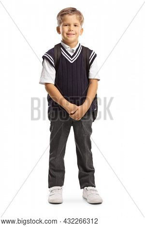 Full length portrait of a cute little schoolboy in a uniform carrying a backpack and smiling at camera isolated on white background