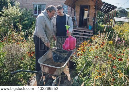 A 30-year-old Man Pours Water Into A Cement Mixture To Create Cement For Pouring Paths In A Garden