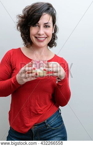 Brazilian Woman With A Big Smile On Her Face, Staring At The Camera And Holding A Mug Of Cappuccino.
