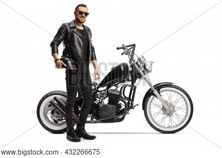 Full length portrait of a biker with a chopper holding helmet and wearing sunglasses isolated on white background