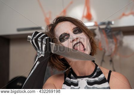 Mad Shaggy Woman With Creepy Makeup In Room Decorated For Halloween Party, Front View. She Licks Sha