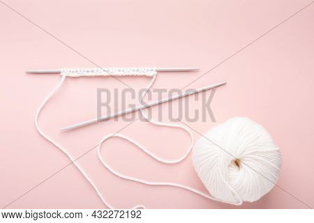 Knitting Project In Progress. White Knitting Wool And Knitting Needles On Pastel Pink Background. Fe