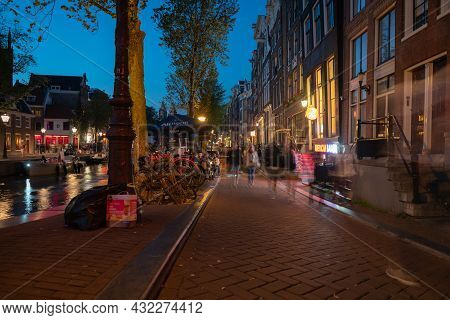 Amsterdam Netherlands - August 17 2017; People Dining By Canal While Others Blurred In Movement Walk