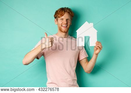 Real Estate Concept. Young Man With Red Hair, Wearing T-shirt, Showing Paper House Cutout And Thumb